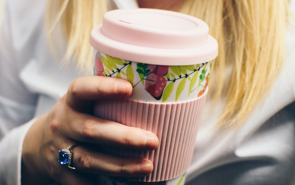 Selective Focus Photography of Woman Holding Pink Floral Plastic Tumbler