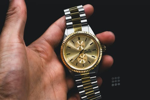 Person Holds Gold Colored Invicta Analog Watch