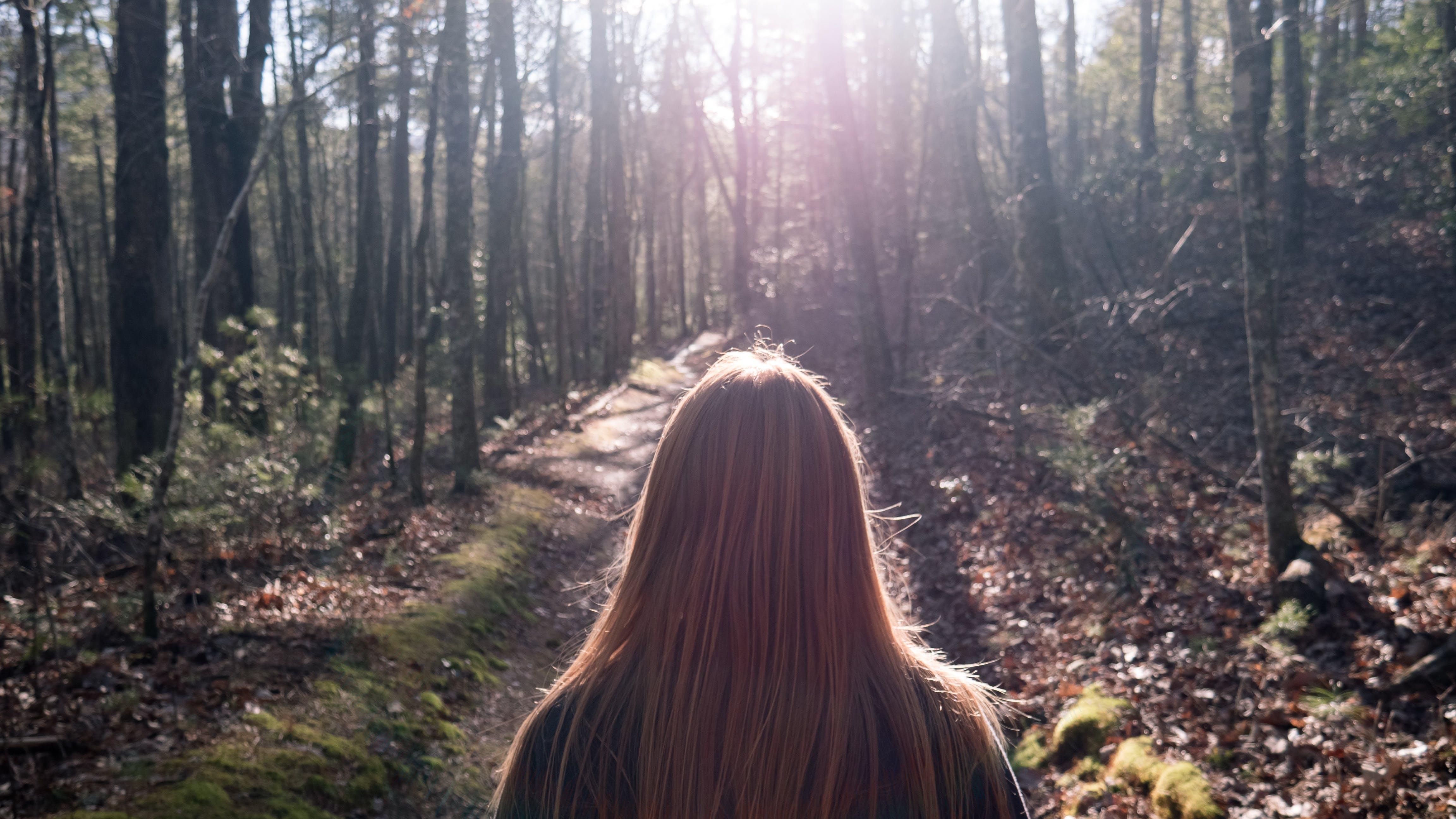 Woman in Black Top Standing Between Trees
