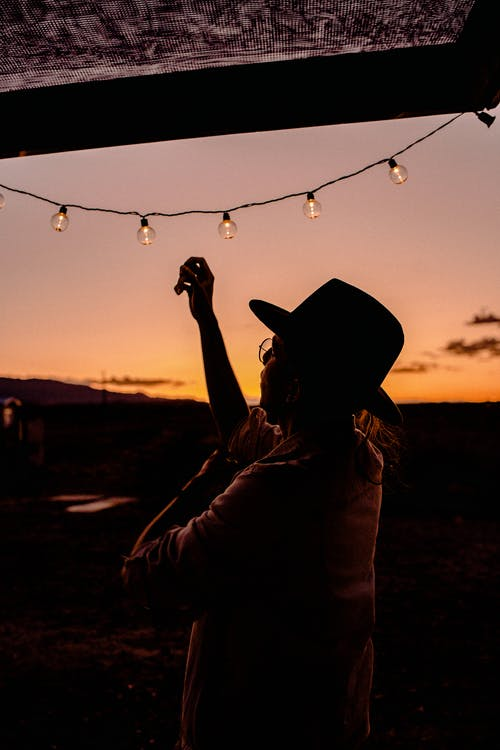 Woman About To Touch String Lights