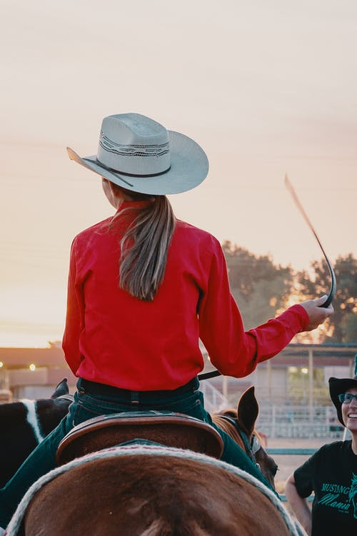 Woman Wearing White Cowboy Hat And Red Top Riding On Horse