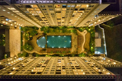 High-angle Photography of Rectangular Green Swimming Pool in Between High-rise Buildings