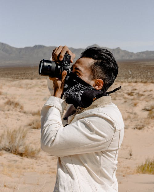 Man Wearing White Denim Jacket Holding Dslr Camera
