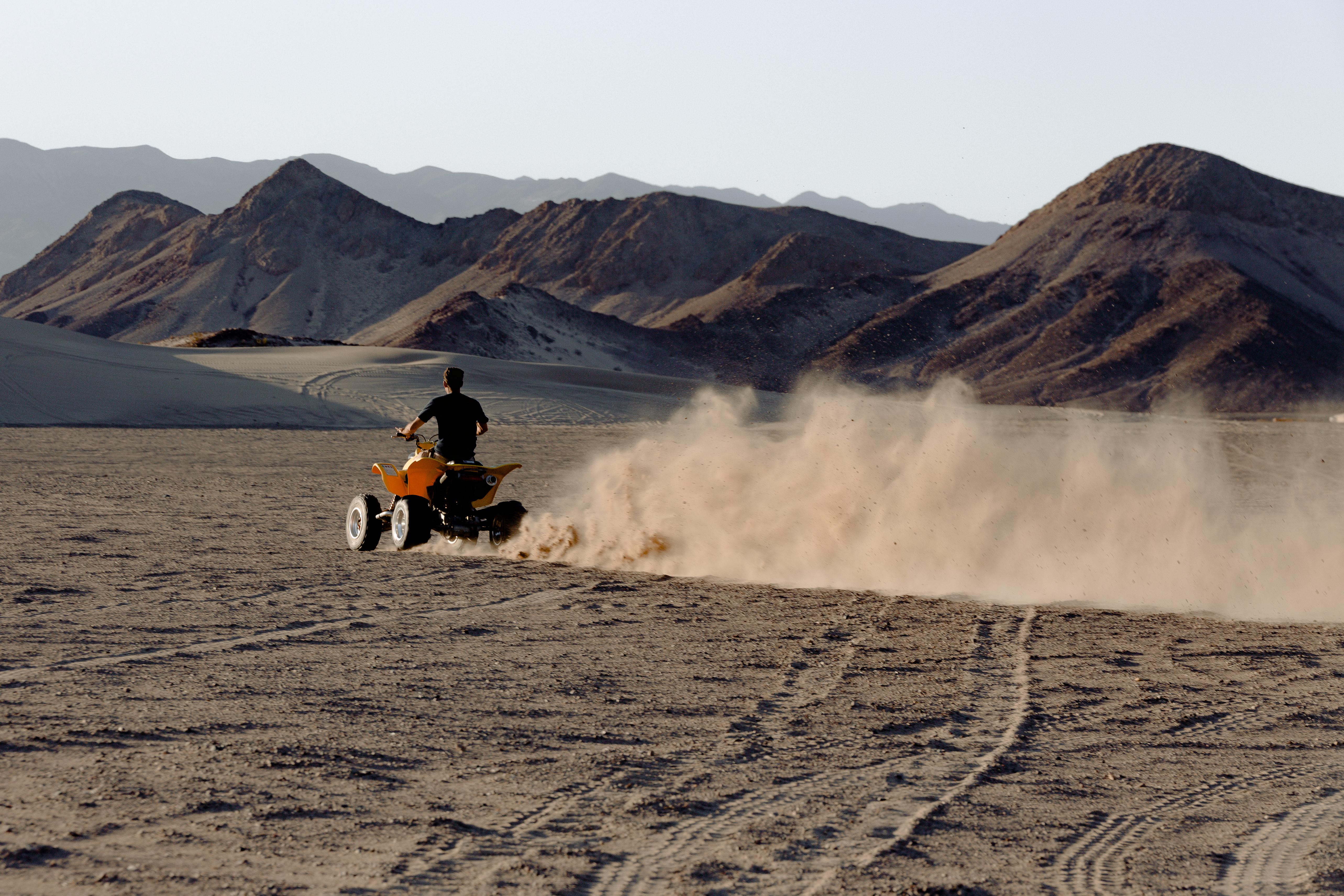 Man Riding Atv in Desert Viewing Mountain