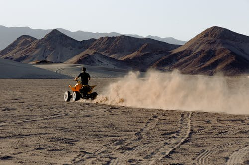 Man Riding Atv in Desert Viewing Mountain