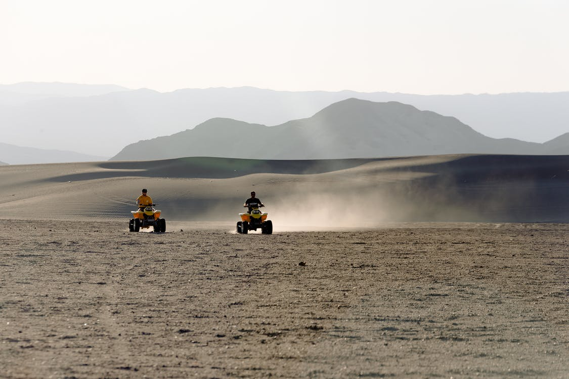 Two People Riding Atv on Desert