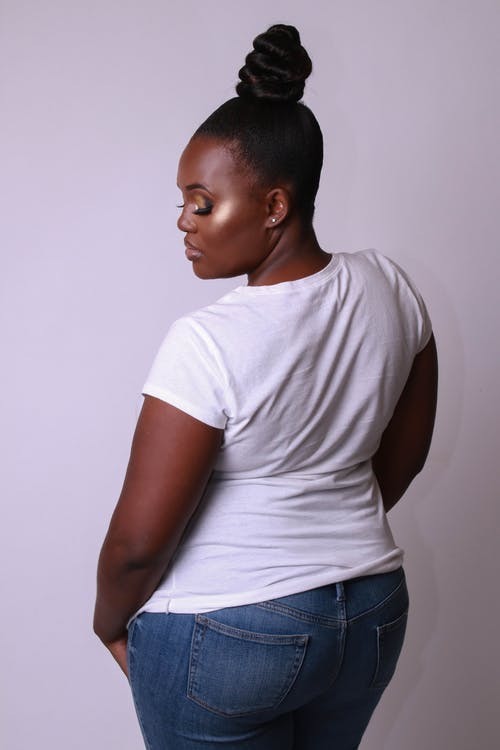 Back View Photo of Woman in White T-shirt and Blue Jeans Posing In Front of White Background