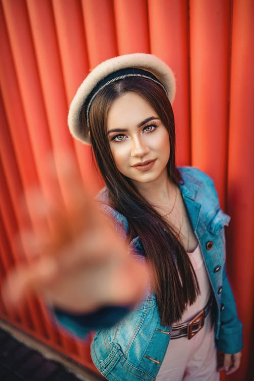 Photo of Woman in Blue Denim Jacket Posing While Reaching Out Her Hand