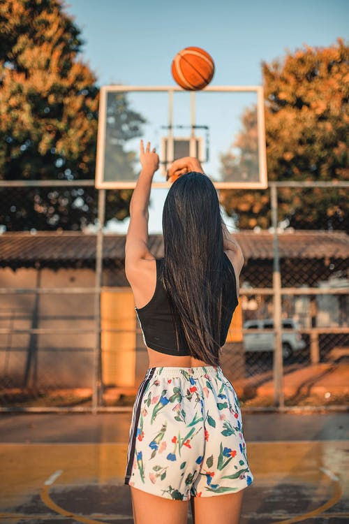 Selective Focus Back View Photo of Woman in Black Top and Floral Shorts Playing Basketball