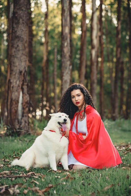 Selective Focus Photo of Woman in Red Cape and White Dress Kneeling Beside White Dog
