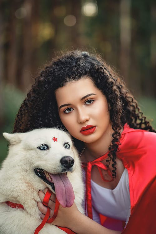 Close-up Photo of Woman in White Dress and Red Cape Posing Next to White Dog
