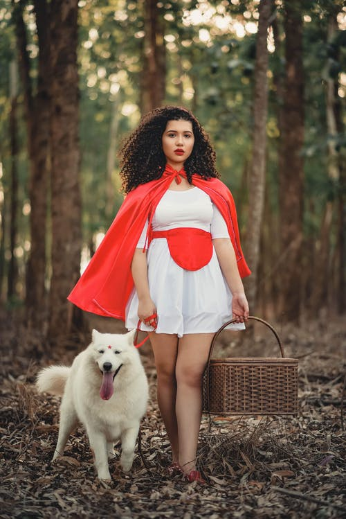 Photo of Woman in White Dress and Red Cape Posing with White Dog While Carrying a Basket