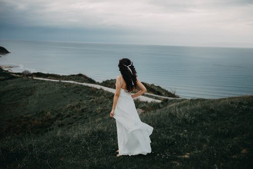 Woman In White Sleeveless Dress Overlooking The Sea