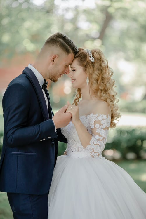 Selective Focus Photo of Groom and Bride Facing Each Other