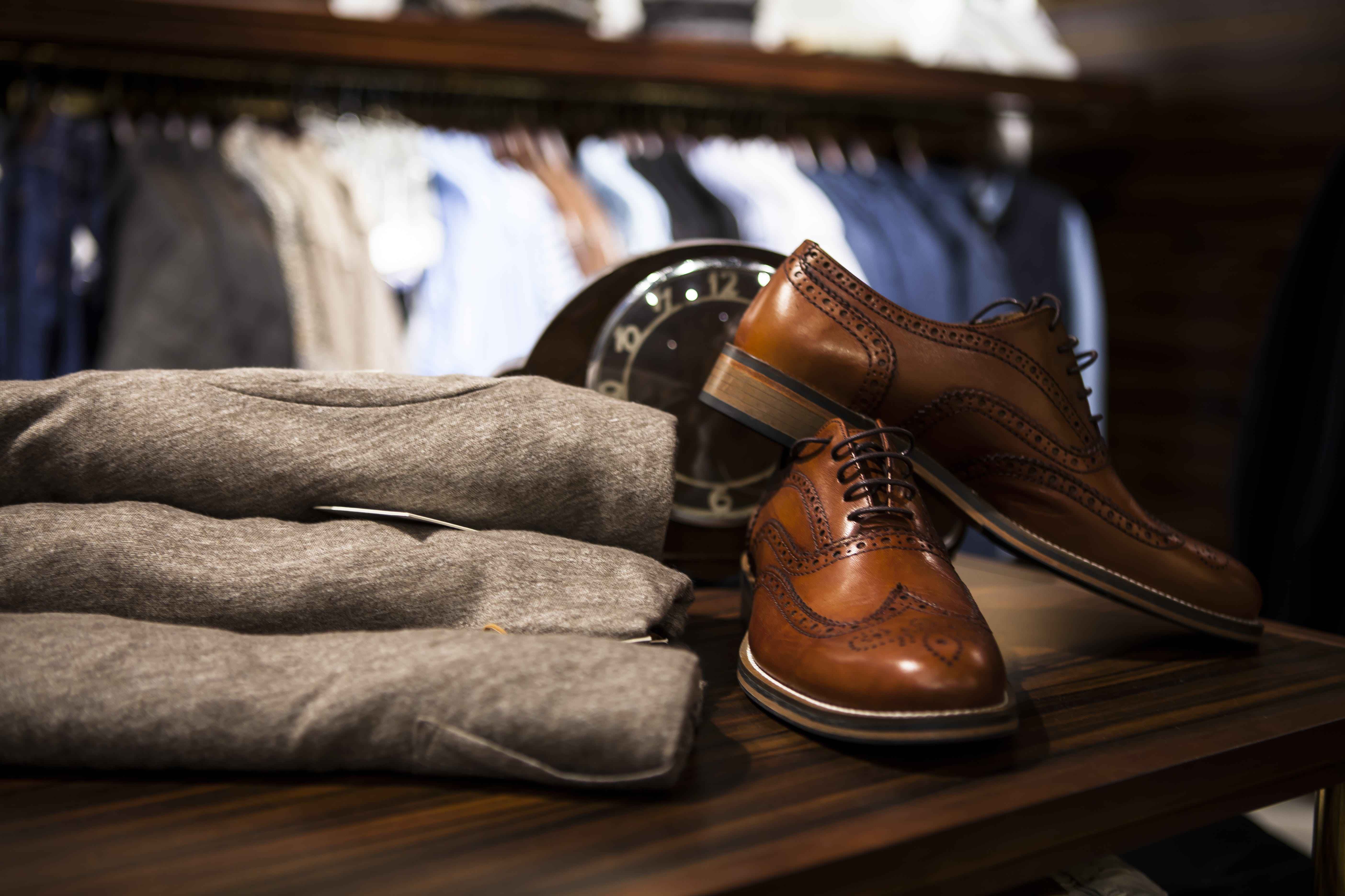 Pair of Brown Leather Wingtip Shoes Beside Gray Apparel on Wooden Surface