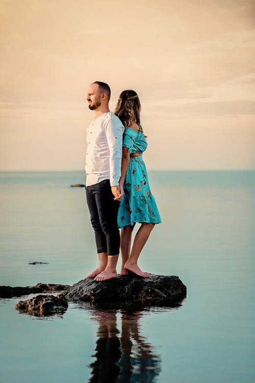 Photo Of Couple Standing On Top Of Rock