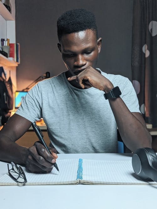 Photo of Man Writing On Notebook