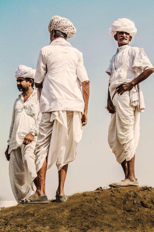 Three Men Standing on Hill