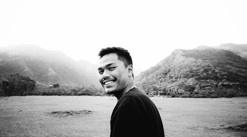 Black and white happy Asian male with toothy smile standing in valley and resting in nature