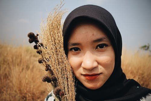 Ethnic woman with bunch of dry grass in field