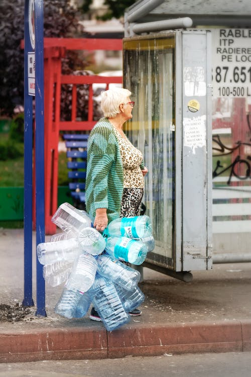 Old Woman Holding Empty Plastic Water Bottles Standing Near Road