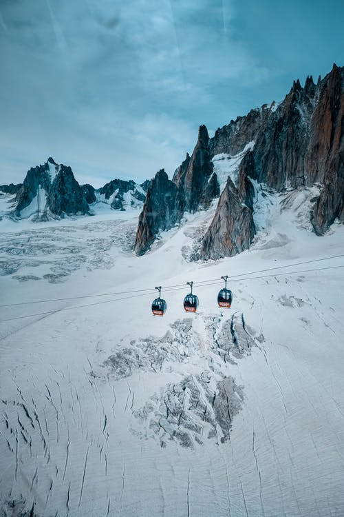 Three Cable Cars over Snow-covered Mountain
