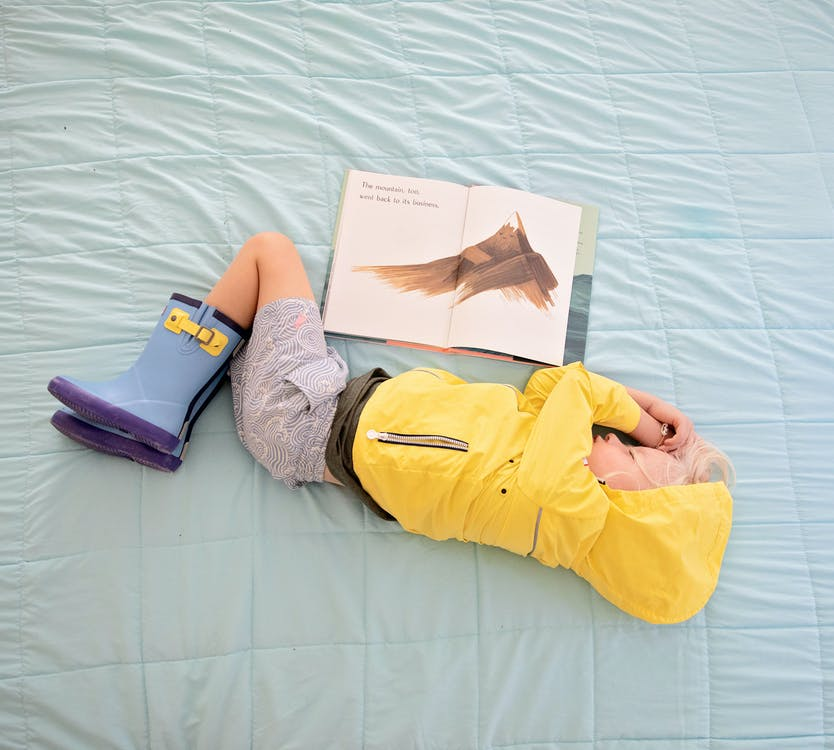 Baby in Yellow Hooded Jacket Sleeping Beside Book