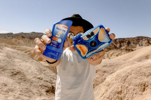 Man Holding Blue Kodak Camera and Sunscreen
