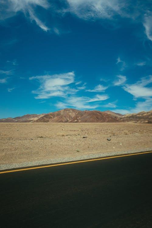 Highway Across Mountain Range Under Blue Sky