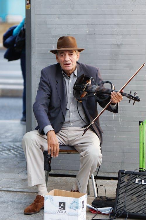 Foto d'estoc gratuïta de assegut, barret, carrer, home