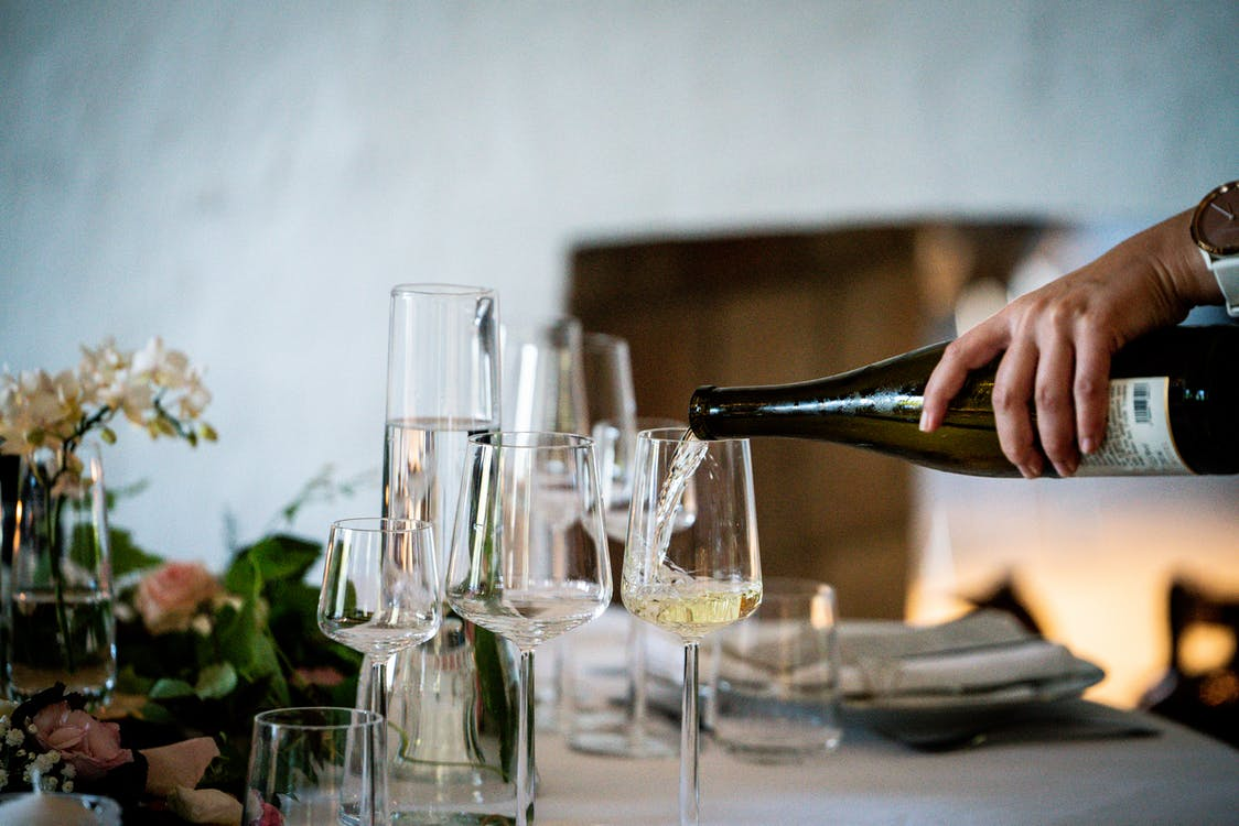 Photo Of Person Pouring Liqueur On Wine Glass