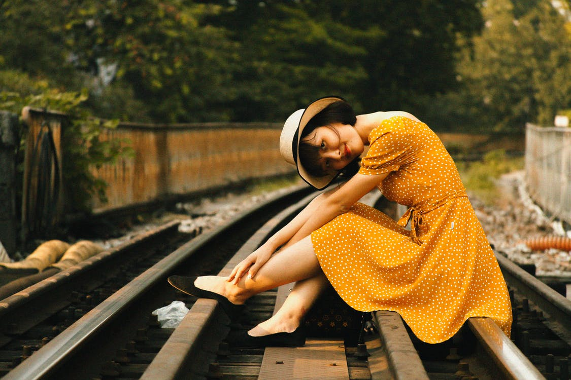 Woman Sitting on Train Tracks
