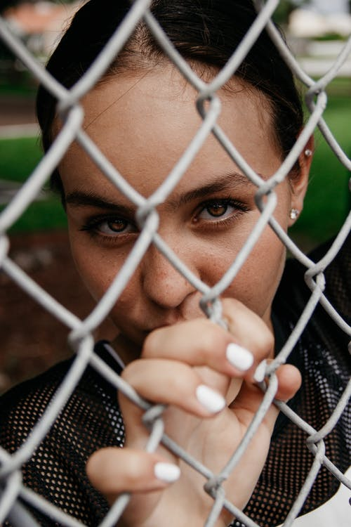 Close-up Portrait Photo of Woman Leaning on Chain-link Fence