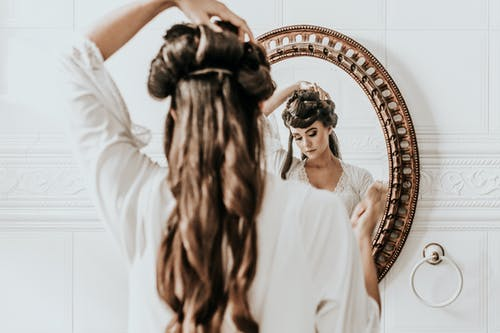 Woman Fixing Her Hair In Front Of A Mirror