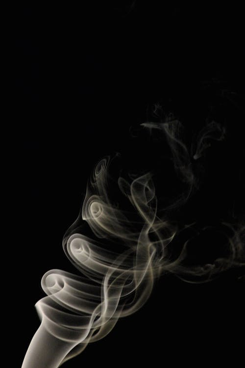 Whiff of thin white fume coiling and rising in dark room on black background