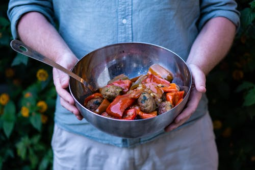 Person Holding Cooked Dish on Gray Stainless Steel Bowl