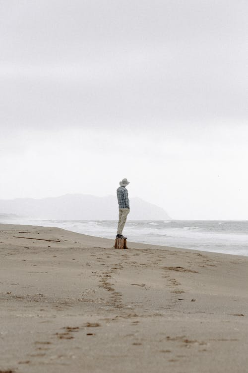 Man in Hat Standing in Seashore