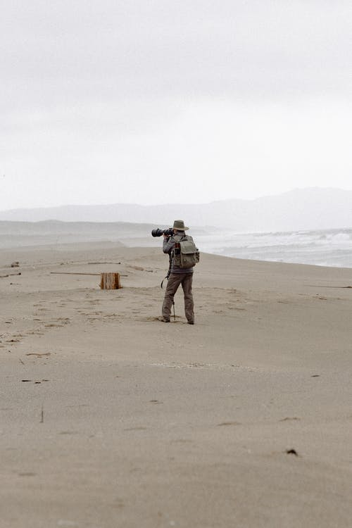 Man Holding Camera Standing on Seashore