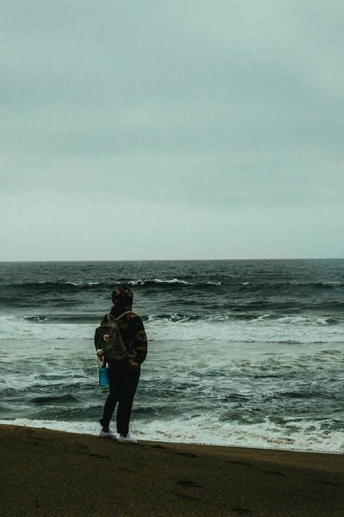 Photo of Person Carrying Backpack Standing Alone on the Beach Overlooking the Horizon