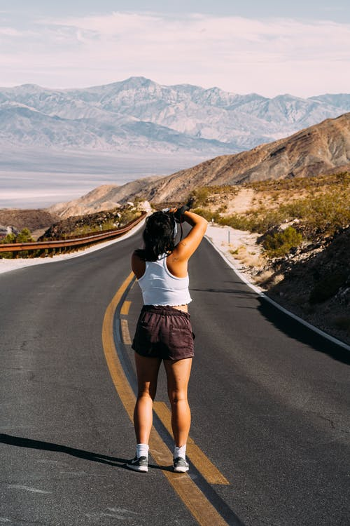 Back View Photo of Woman in White Tank Top and Brown Shorts Standing in the Middle of an Empty Road Taking a Photo