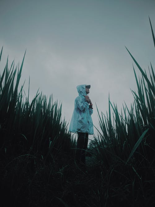 Side View Photo of Person Wearing a Raincoat Standing on Grass Field