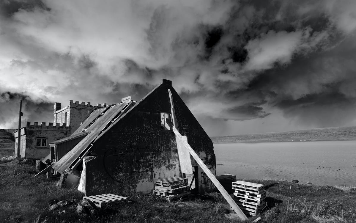 Grayscale Photo of House Under Cloudy Sky