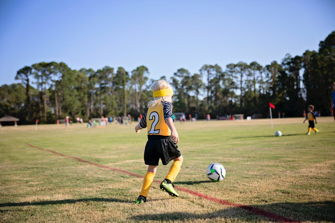 Boy Wearing Yellow and White Jersey Playing Soccer Field