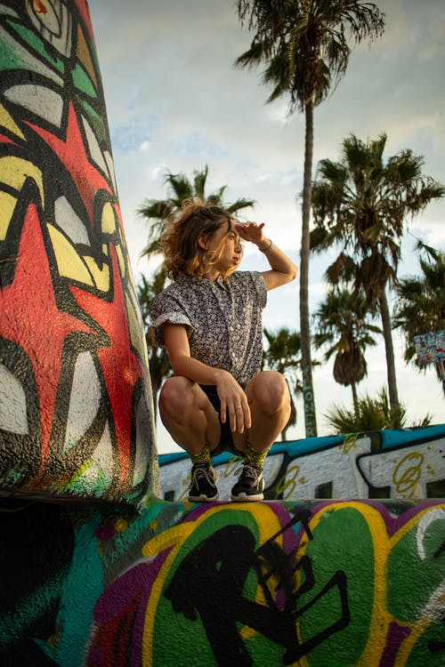 Photo of Woman Squatting on Graffiti Wall Posing While Looking Away