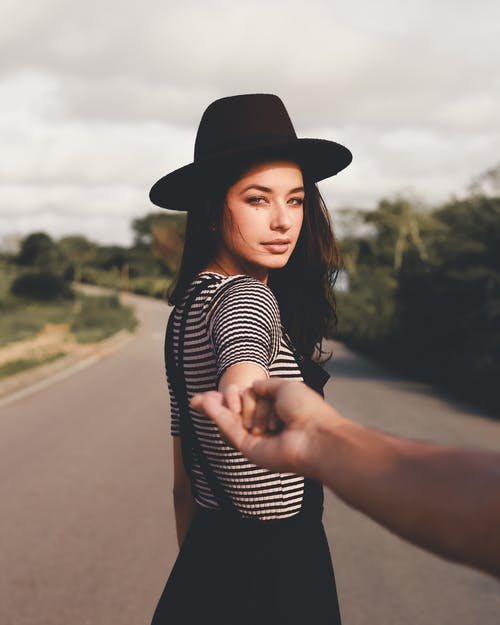 Woman in Black Hat Holding Person's Hand