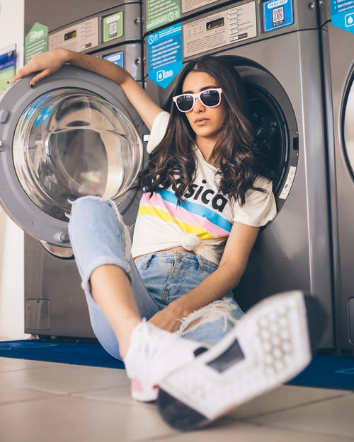 Woman Sitting and Leaning on Washer