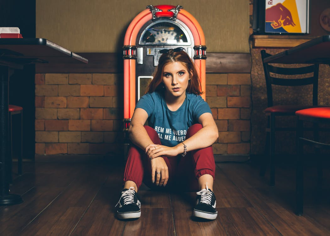 Woman Wearing Blue Shirt and Red Track Pants Sitting Beside of Jukebox