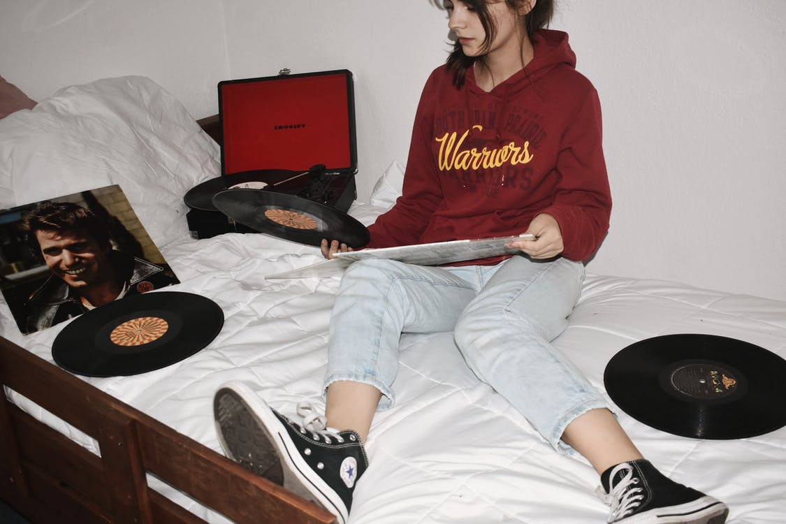 Woman Sitting on Bed Holding Vinyl Records