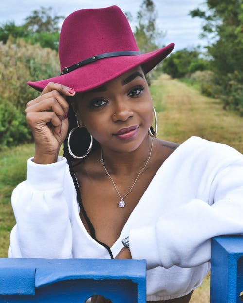 Close-up Photo of Woman in Maroon Fedora Hat and White Top Posing