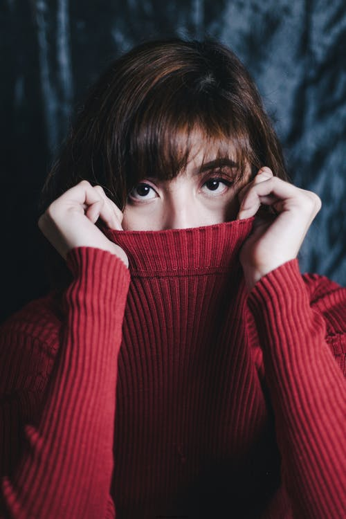 Portrait Photo of Woman Covering Her Mouth With a Red Sweater